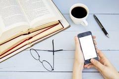Рука молодой женщины держа умный телефон с пустым белым экраном на деревянной предпосылке стоковая фотография