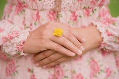 Рука молодой женщины нося желтый цветок представляет обручального кольца Стоковые Фотографии RF