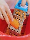 Рука молодой женщины трет морковей на терке в красный шар стоковые фото