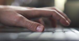 Рука молодого человека используя тетрадь в фокусе кафа или дома очень отмелом Стоковая Фотография