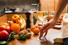 Рука молодой женщины держа бокал вина в кухне стоковая фотография