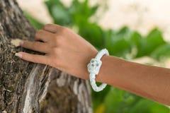 Рука молодой женщины с handmade браслетом кожи на предпосылке дерева Стоковые Фото