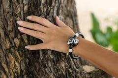 Рука молодой женщины с handmade браслетом кожи на предпосылке дерева Стоковое Изображение RF