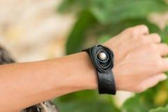 Рука молодой женщины с handmade браслетом кожи на предпосылке дерева Стоковая Фотография