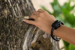 Рука молодой женщины с handmade браслетом кожи на предпосылке дерева Стоковые Изображения RF
