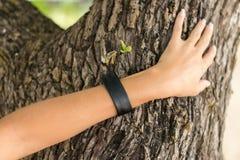 Рука молодой женщины с handmade браслетом кожи на предпосылке дерева Стоковые Фотографии RF