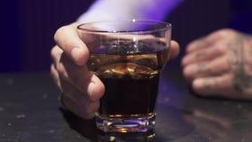 Рука мужчины кладет стекло жидкости алкоголя с льдом на поверхность черной таблицы видеоматериал