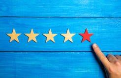 Рука мужчины указывает к пятой красной звезде на голубой деревянной предпосылке 5 звезд Оценка ресторана или гостиницы, применени Стоковое Фото