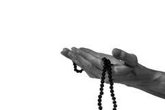 Рука мусульманского человека моля с розарием Стоковая Фотография