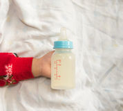 Рука младенца держа бутылку молока Стоковое Изображение RF