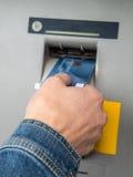 рука наличных дег карточки atm вводя пластичную женщину разведения s стоковые изображения