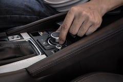 Рука на мультимедиа контролирует кнопки современного автомобиля стоковое фото