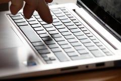 Рука на облегченной клавиатуре компьтер-книжки Стоковые Изображения RF