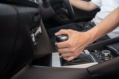 Рука на перенося шестерне на автомобиле, человеке управляя автомобилем стоковое фото rf