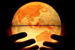 Рука на светлом глобусе стоковые фото