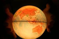 Рука на светлом глобусе стоковая фотография rf