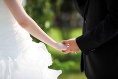 Рука невесты и bridegroom - внутри - рука Стоковое Изображение