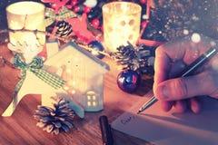 Рука Нового Года пишет на таблице с конусом сосны Стоковое фото RF
