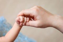 Рука новорожденных ребеят в руке матери ребенок ее мама Стоковые Изображения RF