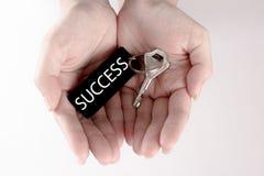 Рука носит серебряный ключ с ярлыком формулировок успеха Ключ к концепции успеха изолированной в белой предпосылке Стоковые Изображения RF
