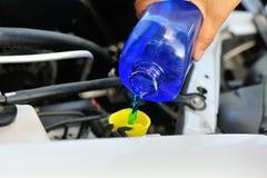 Рука добавляя автоматического стеклянного уборщика для автомобиля стоковое изображение rf