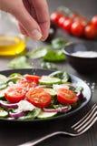 Рука добавляя соль к vegetable салату стоковые изображения