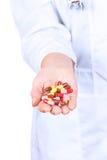 Рука доктора держа много таблеток желтого цвета Стоковая Фотография