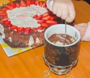 Рука окунула плодоовощ в фондю десерта, конце-вверх Стоковое фото RF