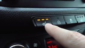 Рука отжимает нагретую кнопку места высокую на приборной панели в автомобиле видеоматериал