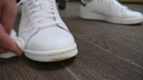 Рука очищая грязные белые ботинки видеоматериал