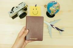 Рука пасспорта владением женщины имеет плоскую модель, ретро камеру, worl Стоковые Фотографии RF