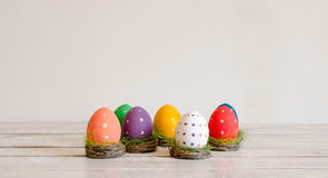 Рука пасхальных яя покрасила сидеть в гнездах на белой предпосылке пасха счастливая Стоковые Фотографии RF