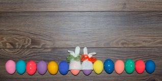 Рука пасхальных яя покрашенная с связанными шляпами зайчика над деревянной предпосылкой с космосом экземпляра пасха счастливая Стоковое Изображение