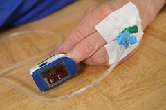 Рука пациента с ИМПом ульс oximetry стоковая фотография