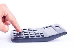 Рука пальца положила калькулятор кнопки для высчитывать дело бухгалтерского учета номеров учитывая на белую предпосылку si Стоковое Изображение