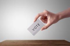 Рука персоны давая его голосование в урне для избирательных бюллетеней стоковые изображения