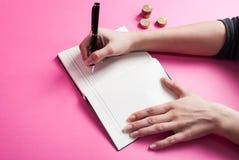 Рука пишет в монетке тетради и металла на розовой предпосылке стоковое изображение rf