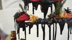 Рука поворачивает дальше вращая украшенный торт стойки сток-видео