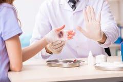 Рука повредила traumatologist доктора женщины посещая стоковое фото rf