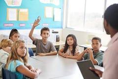 Рука повышения школьника, который нужно ответить в класс начальной школы стоковое фото rf