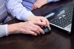 Рука пожилой руки женщины и мальчика держа мышь компьютера Стоковые Фотографии RF