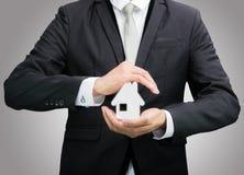 Рука позиции бизнесмена стоящая держа значок дома изолированный стоковые фото