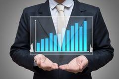 Рука позиции бизнесмена стоящая держа финансы диаграммы изолированный на серой предпосылке Стоковые Изображения