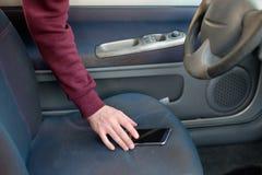 Рука похитителя крадя мобильный телефон от припаркованного автомобиля Стоковая Фотография