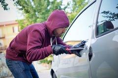 Рука похитителя крадя мобильный телефон от припаркованного автомобиля Стоковая Фотография RF