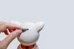 Рука положила монетку в банк монетки Стоковое Фото