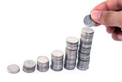 Рука положила монетку к деньгам Стоковые Изображения