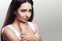 рука предпосылки изолированная над женщиной больной боли в горле места белой Девушка держит ее оружия в горле холодно anglia Тяго стоковое фото