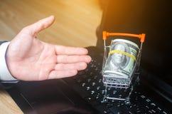 рука представляет тележку супермаркета на компьтер-книжке Концепция ходить по магазинам онлайн Установите рынок, коммерцию, комме стоковое фото rf