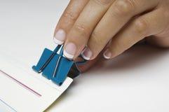 Рука прикрепляя бумажный зажим связывателя Стоковое Фото